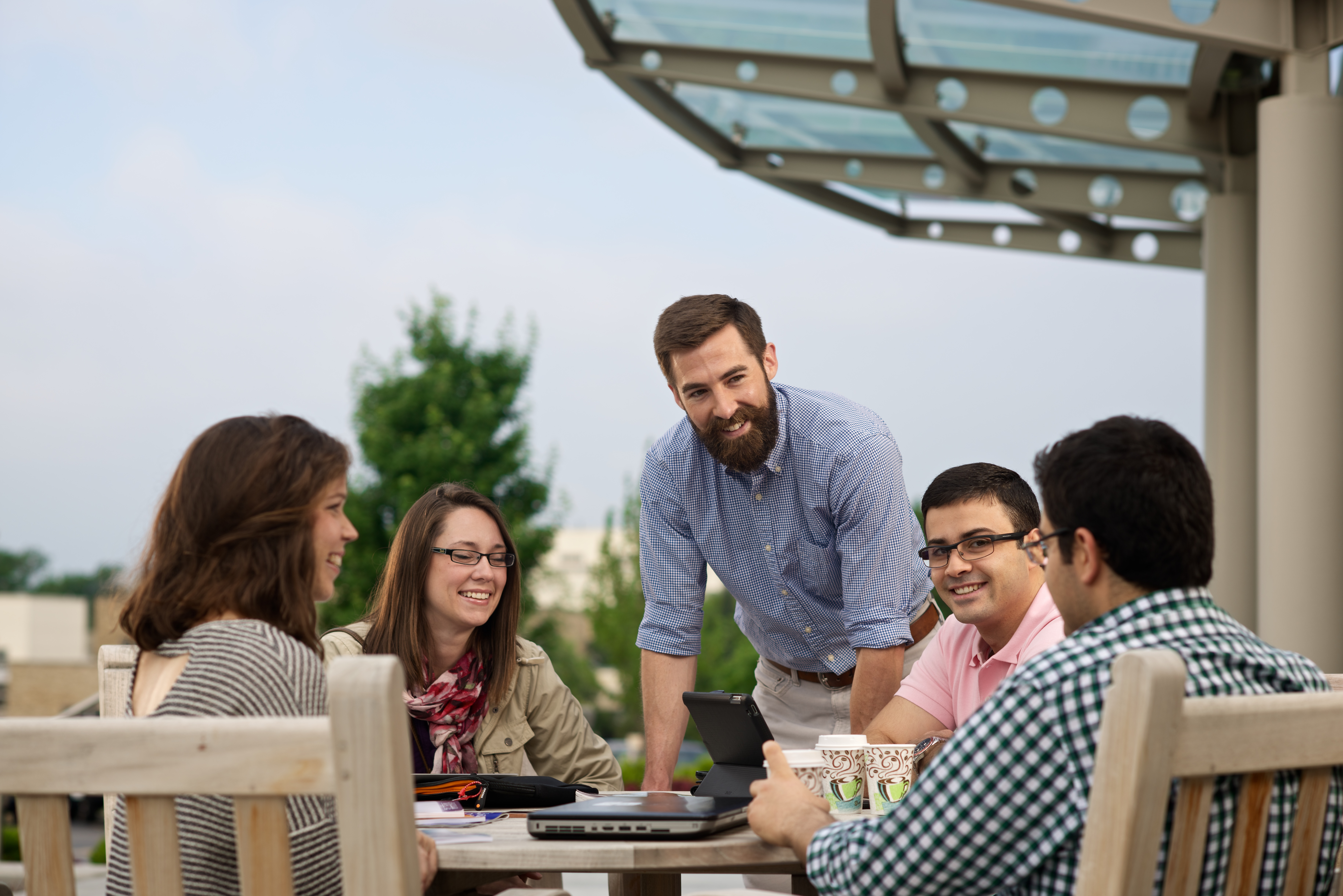 Employees collaborating around a table on the OU-Tulsa campus.
