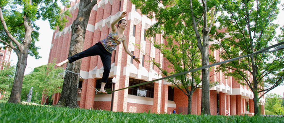 Female student walking a tight rope in front of the Bizell Library